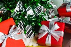 Ciérrese encima de la caja de regalo roja y blanca en la tabla de madera con el árbol de pino y el fondo del cono del pino Imagen de archivo