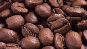 Ciérrese encima de la cantidad de girar los granos de café asados almacen de video