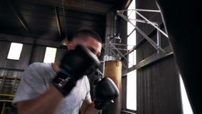 Ciérrese encima de la cantidad de un boxeador de sexo masculino que se resuelve en gimnasio, entrenando a proceso con el saco de  almacen de video