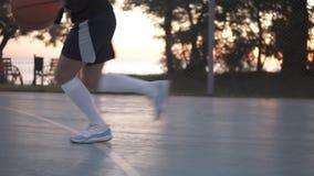 Ciérrese encima de la cantidad de un jugador de básquet de la chica joven que entrena y que ejercita al aire libre en la corte lo almacen de video