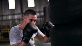 Ciérrese encima de la cantidad de un proceso masculino del entrenamiento del boxeador Golpeando el coche con el pie pone un neumá almacen de metraje de vídeo