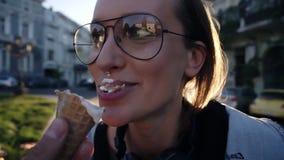 Ciérrese encima de la cantidad de una cara de la mujer joven en los vidrios que comen un helado de la mano del malee Amistad, div almacen de video