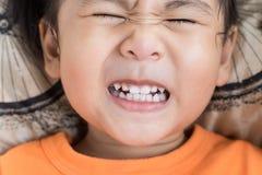 Ciérrese encima de la cara divertida de la actuación dentuda de los niños foto de archivo