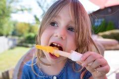 Ciérrese encima de la cara de la muchacha que come el polo de hielo anaranjado Foto de archivo