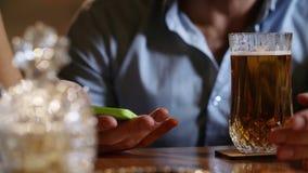 Ciérrese encima de la cerveza de consumición sola del hombre y smartphone con mientras que se sienta en barra de lujo almacen de metraje de vídeo