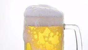 Ciérrese encima de la cerveza de cerveza dorada de colada en vidrio sobre blanco almacen de video