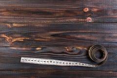 Ciérrese encima de la cinta métrica del sastre en fondo de madera de la tabla Departamento bajo de la cinta métrica blanca del ca Fotos de archivo libres de regalías