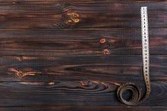 Ciérrese encima de la cinta métrica del sastre en fondo de madera de la tabla Departamento bajo de la cinta métrica blanca del ca Imagenes de archivo