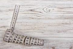 Ciérrese encima de la cinta métrica del sastre en fondo de madera de la tabla Departamento bajo de la cinta métrica blanca del ca Fotografía de archivo libre de regalías