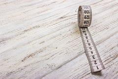 Ciérrese encima de la cinta métrica del sastre en fondo de madera de la tabla Departamento bajo de la cinta métrica blanca del ca Foto de archivo