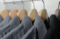 Ciérrese encima de la fila de las camisas grises y negras que cuelgan en la suspensión de capa Imágenes de archivo libres de regalías