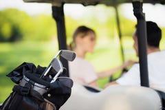 Ciérrese encima de la foto Clubs de golf en el primero plano, hombre con una mujer en un carro de golf en un fondo Imágenes de archivo libres de regalías