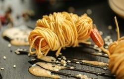 Ciérrese encima de la foto de la comida de las gambas fritas del tigre en tallarines de huevo en fondo negro de la pizarra Cultur Foto de archivo