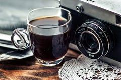 Ciérrese encima de la foto de la lente vieja, del vintage de cámara con el casquillo del café y de fotos blancos y negros sobre l foto de archivo libre de regalías