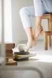 Ciérrese encima de la foto de los libros y de la taza de café que mienten en piso Piernas del ` s de la muchacha en fondo de la s Foto de archivo