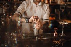 Ciérrese encima de la foto de un camarero que se coloca en la coctelera que se sostiene contraria Imágenes de archivo libres de regalías