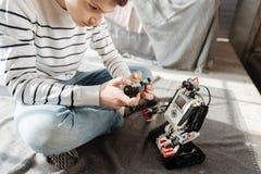Ciérrese encima de la foto del adolescente serio mientras que juega con el robot Fotos de archivo libres de regalías