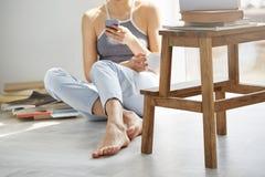 Ciérrese encima de la foto del web que practica surf del adolescente joven en el teléfono que sostiene la taza que se sienta en p Imágenes de archivo libres de regalías