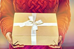Ciérrese encima de la foto de la mano de la mujer que sostiene la caja de regalo de papel en fondo rojo hecho punto del suéter Foto de archivo libre de regalías