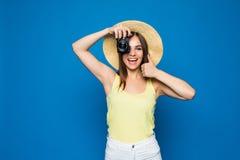 Ciérrese encima de la foto de la mujer en sombrero en el azul que toma una foto con la cámara digital Foto de archivo