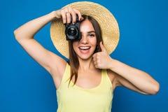 Ciérrese encima de la foto de la mujer en sombrero en el azul que toma una foto con la cámara digital Imagen de archivo libre de regalías