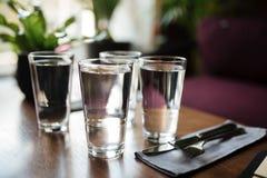 Ciérrese encima de la foto de vidrios con agua en la tabla en restaurante Cuatro vidrios con agua y el cuchillo con la bifurcació Imagen de archivo libre de regalías