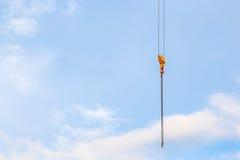 Ciérrese encima de la grúa con un gancho en el extremo en el fondo del cielo azul Fotografía de archivo libre de regalías