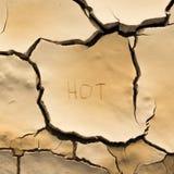 Ciérrese encima de la grieta y del suelo seco con la palabra caliente Imagenes de archivo