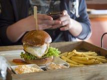 Ciérrese encima de la hamburguesa grande con el huevo frito, las patatas fritas y la barbacoa Foto de archivo libre de regalías