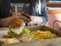 Ciérrese encima de la hamburguesa grande con el huevo frito, las patatas fritas y la barbacoa Imagen de archivo libre de regalías