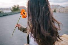 Ciérrese encima de la imagen de la chica joven con la flor anaranjada Fotos de archivo libres de regalías