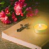 Ciérrese encima de la imagen de dios y de la luz de una vela de la cruz del metal en el pap clásico Imágenes de archivo libres de regalías