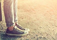 Ciérrese encima de la imagen de la muchacha en las zapatillas de deporte que se sientan en el banco Fotos de archivo