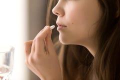 Ciérrese encima de la imagen de la mujer que bebe alrededor de la píldora blanca fotos de archivo