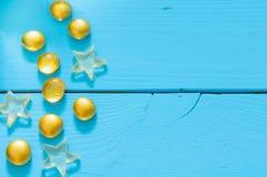 Ciérrese encima de la imagen de mármoles amarillos en fondo de madera azul imagenes de archivo