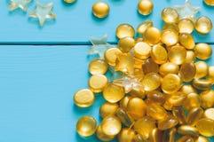 Ciérrese encima de la imagen de mármoles amarillos en fondo de madera azul foto de archivo libre de regalías