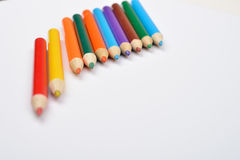 Ciérrese encima de la imagen de muchos pequeños creyones coloreados del lápiz en blanco Fotografía de archivo