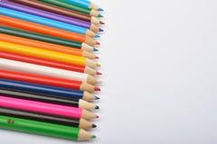 Ciérrese encima de la imagen de muchos pequeños creyones coloreados del lápiz en blanco Imagen de archivo libre de regalías