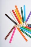 Ciérrese encima de la imagen de muchos pequeños creyones coloreados del lápiz en blanco Foto de archivo libre de regalías