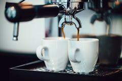 Ciérrese encima de la imagen del café express que vierte en las tazas blancas Fotografía de archivo