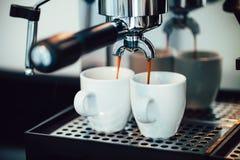 Ciérrese encima de la imagen del café express que vierte en las tazas blancas Fotografía de archivo libre de regalías