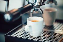 Ciérrese encima de la imagen del café express que vierte en las tazas blancas Fotos de archivo libres de regalías