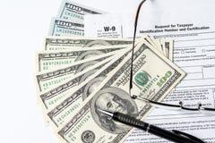 Ciérrese encima de la imagen del dinero, de $100 cuentas, de la forma W-9, de vidrios y de una pluma Imagen de archivo