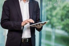 Ciérrese encima de la imagen del hombre de negocios que sostiene una tableta digital, retrato Foto de archivo libre de regalías
