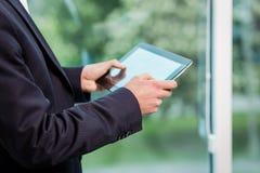 Ciérrese encima de la imagen del hombre de negocios que sostiene una tableta digital, retrato Fotografía de archivo