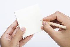 Ciérrese encima de la imagen del lápiz del asimiento de la mano y de la nota pegajosa Fotos de archivo