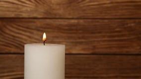 Ciérrese encima de la llama temblante de la vela blanca sobre la madera almacen de metraje de vídeo