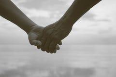 Ciérrese encima de la mano de los pares mayores que mantienen la mano unida cerca de la playa en la playa, color blanco y negro d Fotografía de archivo libre de regalías