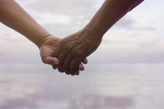 Ciérrese encima de la mano de los pares mayores que mantienen la mano unida cerca de la playa en la playa, imagen filtrada, efect Imágenes de archivo libres de regalías