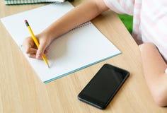 Ciérrese encima de la mano del adolescente de la muchacha que aprende en línea con el teléfono móvil Fotografía de archivo